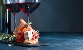 Sandwich with prosciutto, blue cheese and rosemary on a dark background. Glasses and bottle of red wine with snack. Copy space for your text.