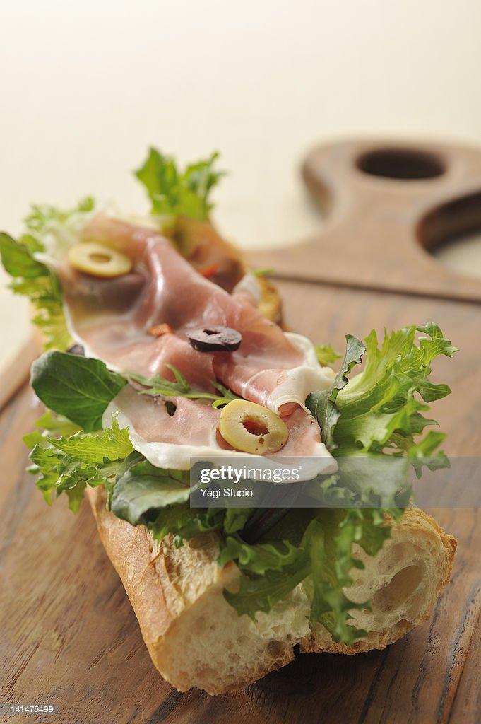Sandwich with prosciutto ham ham and cut olive : Stock Photo