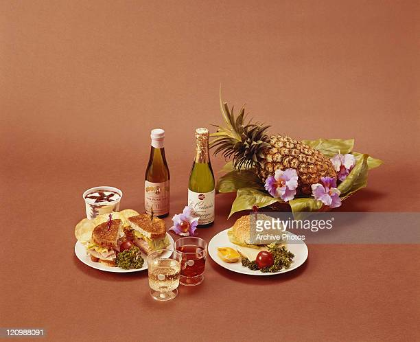 Sandwich with wine, champagne and pineapple on orange background