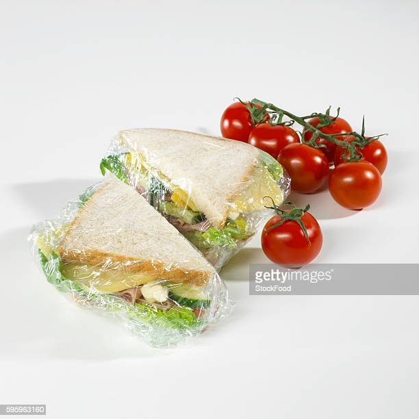 Sandwiches in clingfilm, tomatoes beside them