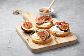sandwiches with figs, ricotta, honey and thyme on a gray background
