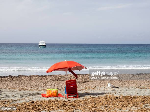 Sandy beach with an umbrella, chair and towel on the island of Tabarca, Alicante, Valencian Community, Spain.