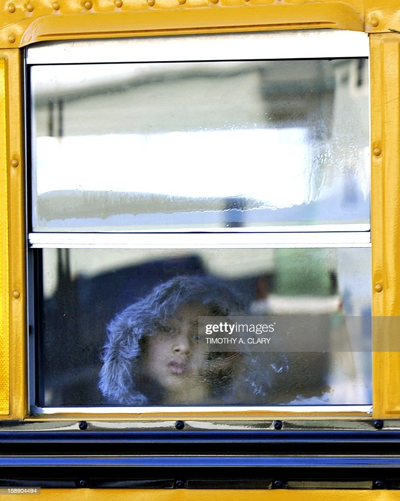 A Sandy Hook Elementry student leaves on a school bus in Newtown, Connecticut on January 3, 2013. Students at the elementary school where a gunman massacred 26 children and teachers last month were returning Thursday to classes at an alternative campus described by police as 'the safest school in America.' Survivors were finally to start their new academic year in the nearby town of Monroe, where a disused middle school has been converted and renamed from its original Chalk Hill to Sandy Hook. AFP PHOTO / TIMOTHY A. CLARY