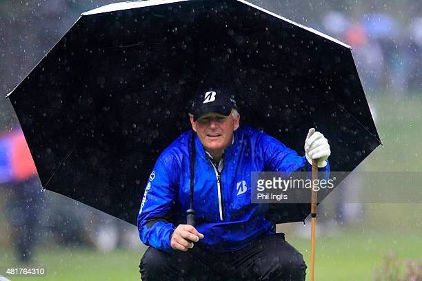 Sandy Lyle of Scotland shelters under his umbrella during the second round of the Senior Open Championship played at The Old Course Sunningdale Golf...