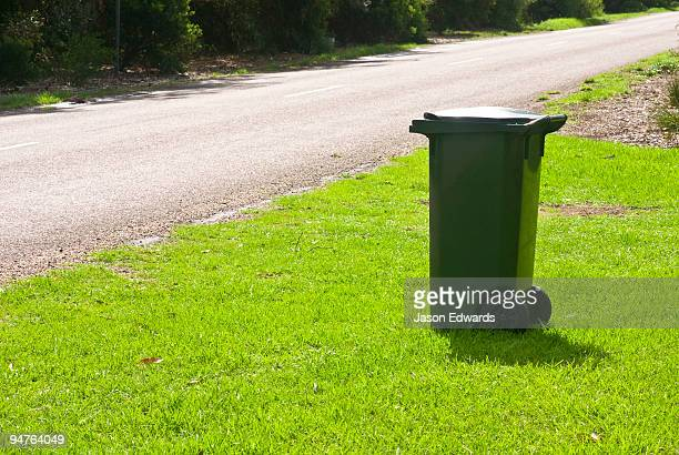 A council garbage bin waits by the road for collection in a rural town