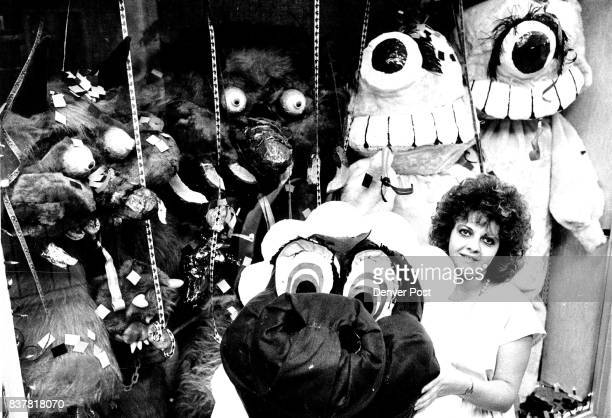 Sandy Wamboldt and her Costume in Window of Woolworth's She is planning on wearing the one she is holding which is a baby dinosaur She made all the...