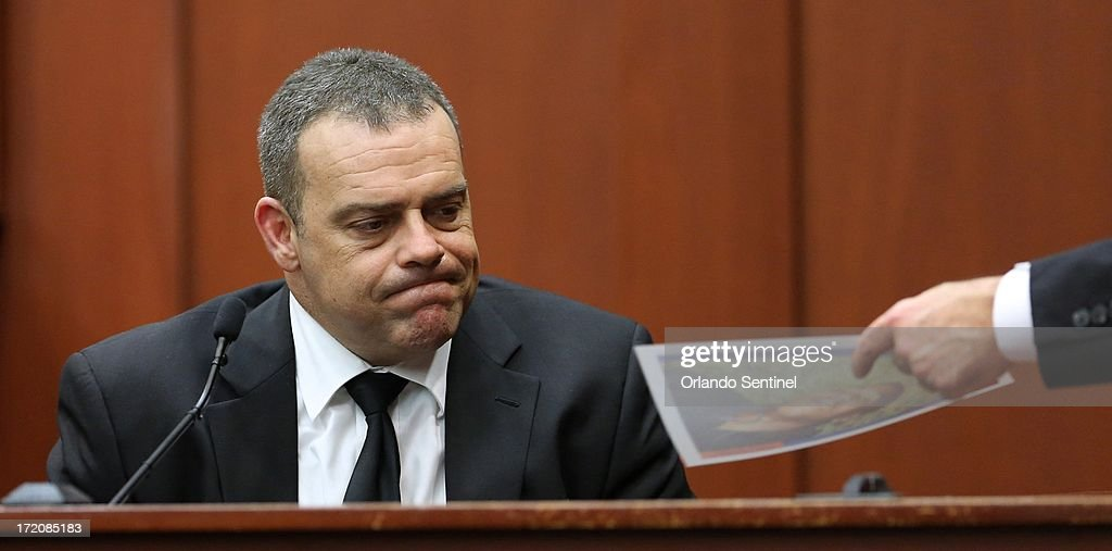 Sanford police officer Chris Serino is shown a photo of a slain Trayvon Martin from the night of the shooting, by prosecutor Bernie de la Rionda while testifying in the trial of George Zimmerman in Sanford, Florida, Monday, July 1, 2013. Zimmerman is accused in the fatal shooting of Trayvon Martin.