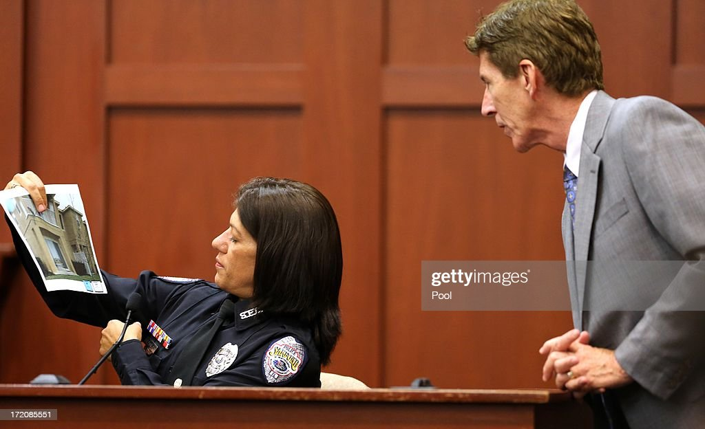 Sanford police officer Doris Singleton, with defense attorney Mark O'Mara, holds up a copy of a photo of the complex where the Trayvon Martin shooting took place, while testifying in Seminole circuit court July 1, 2013 in Sanford, Florida. Zimmerman is charged with second-degree murder for the February 2012 shooting death of 17-year-old Trayvon Martin.