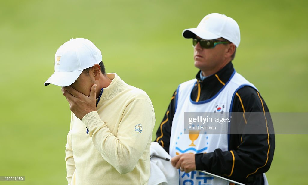 Sang-Moon Bae of the International Team reacts to a poor pitch shot on the 18h hole in his match against Bill Haas of the United States Team as his caddie Matt Minister looks on during the Sunday singles matches at The Presidents Cup at Jack Nicklaus Golf Club Korea on October 11, 2015 in Songdo IBD, Incheon City, South Korea.