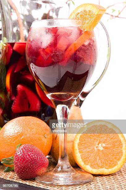 A sangria in a glass with oranges and a pitcher
