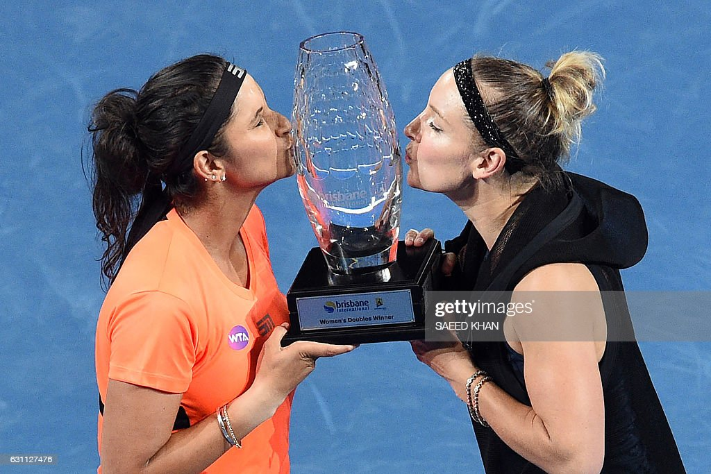 Sania Mirza of India (L) and Bethanie Mattek-Sands of the US kiss their trophy after beating Russia's Ekaterina Makarova and Elena Vesnina in their women's doubles final match at the Brisbane International tennis tournament in Brisbane on January 7, 2017. / AFP / Saeed KHAN / IMAGE