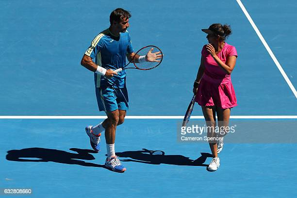 Sania Mirza of India and Ivan Dodig of Croatia talk tactics against Samantha Stosur and Sam Groth of Australia in their mixed doubles semifinal match...