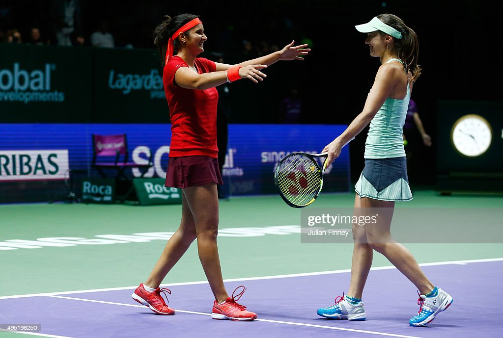 Sania Mirza of India and Martina Hingis of Switzerland celebrate match point during their doubles final match against Carla Suarez Navarro and Garbine Muguruza of Spain during the BNP Paribas WTA Finals at Singapore Sports Hub on November 1, 2015 in Singapore.