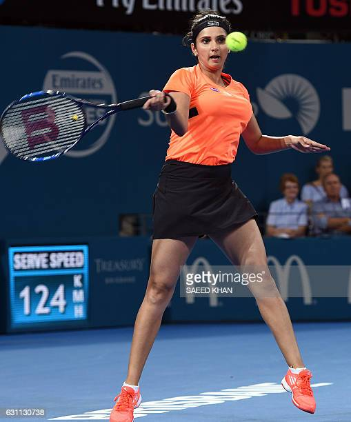 Sania Mirza of India hits a return against Russia's Ekaterina Makarova and Elena Vesnina in their women's double final match at the Brisbane...