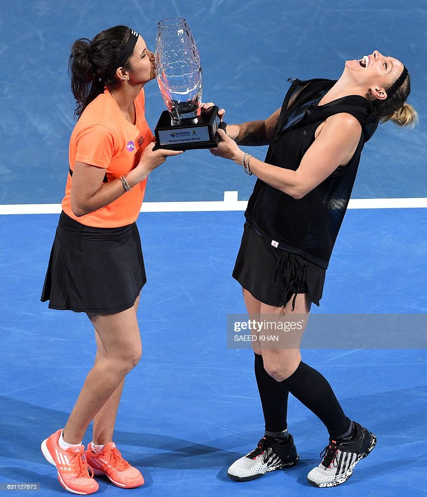 Sania Mirza of India (L) kisses the trophy as Bethanie Mattek-Sands of the US reacts after their victory over Russia's Ekaterina Makarova and Elena Vesnina in their women's doubles final match at the Brisbane International tennis tournament in Brisbane on January 7, 2017. / AFP / Saeed KHAN / IMAGE