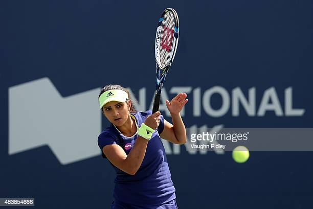 Sania Mirza of India plays a shot against Julia Goerges of Germany and Klaudia JansIgnacik of Germany in a doubles match with partner Martina Hingis...
