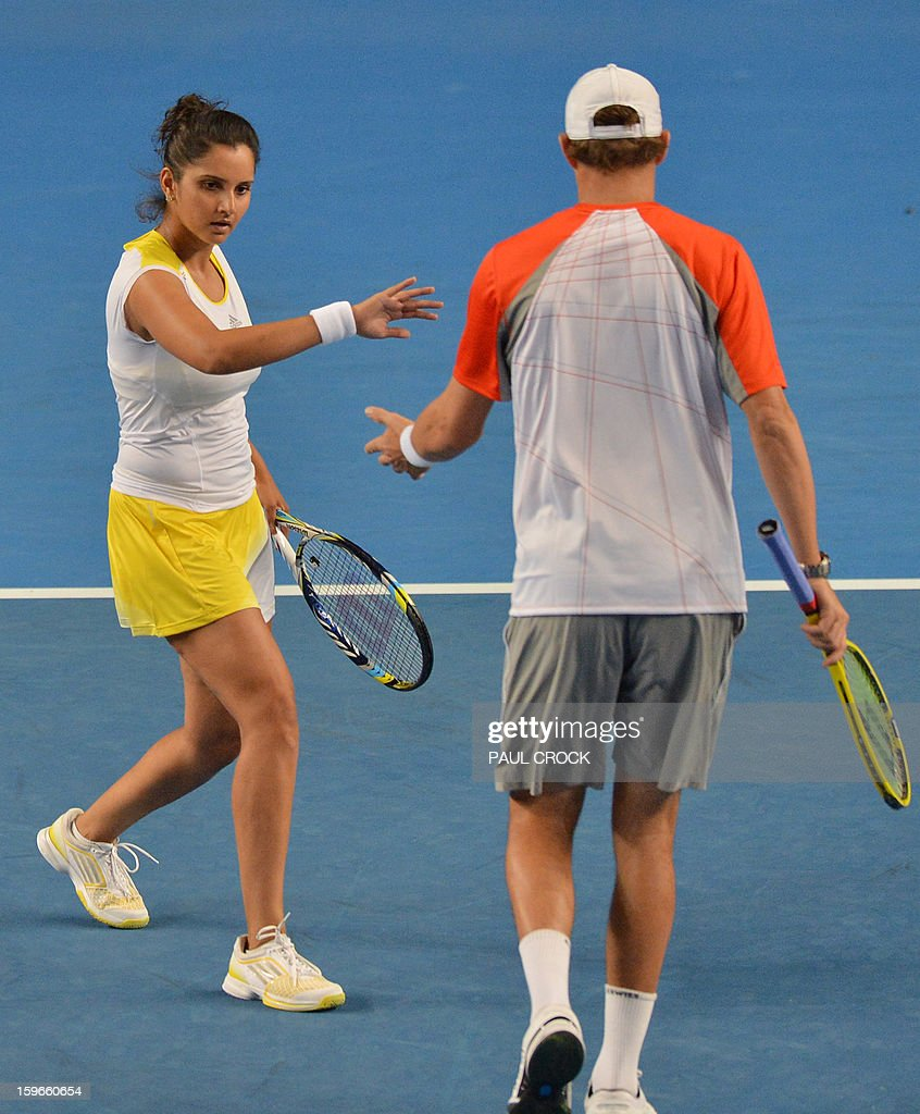 Sania Mirza of India (L) touches hands with playing partner Bob Bryan of the US during their mixed doubles match against Samantha Stosur and Luke Saville of Australia on the fifth day of the Australian Open tennis tournament in Melbourne on January 18, 2013. AFP PHOTO/PAUL CROCK IMAGE STRICTLY RESTRICTED TO EDITORIAL USE - STRICTLY NO COMMERCIAL USE