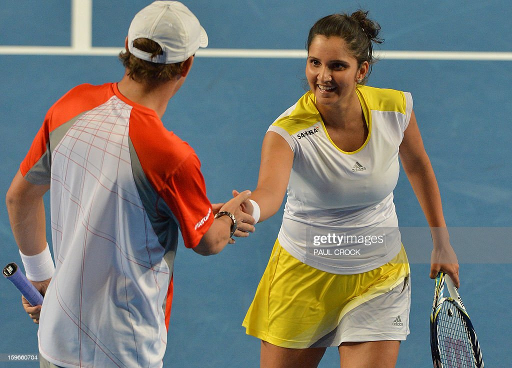 Sania Mirza of India (R) touches hands with playing partner Bob Bryan of the US during their mixed doubles match against Samantha Stosur and Luke Saville of Australia on the fifth day of the Australian Open tennis tournament in Melbourne on January 18, 2013. AFP PHOTO/PAUL CROCK IMAGE STRICTLY RESTRICTED TO EDITORIAL USE - STRICTLY NO COMMERCIAL USE