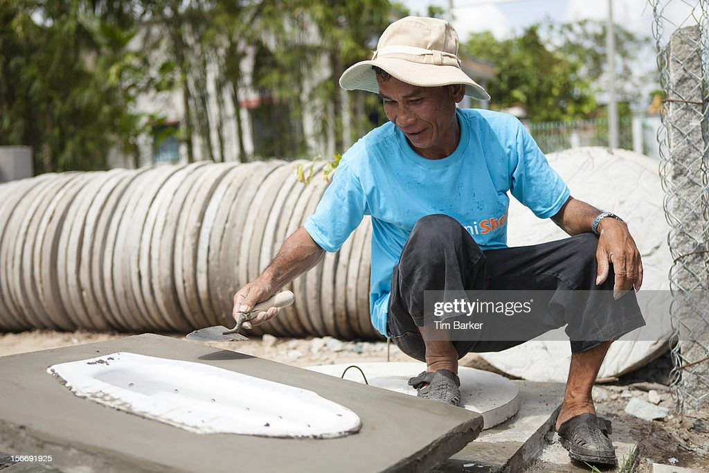 Sanishop employee Nguyen Thanh Liem finishes off a toilet at the Toilet Production Center as part of a media briefing on World Toilet Day on November 19, 2012 in Vinh Long, Vietnam.