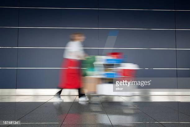 Sanitation worker pushing cleaning cart.