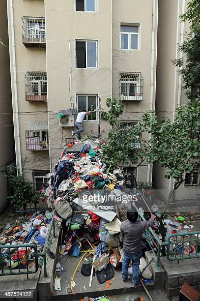 Sanitation workers clean up the waste removed from a fourth storey apartment on September 9 2015 in Qingdao Shandong Province of China The build up...