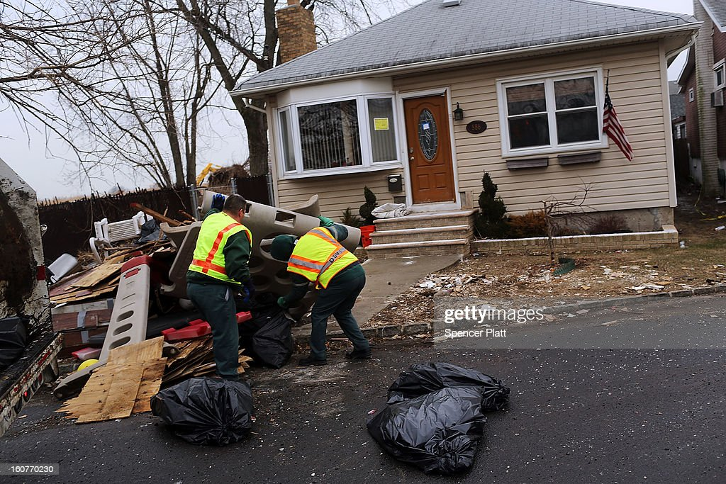 Sanitation workers throw out debris from a flood damaged home in Oakwood Beach in Staten Island on February 5, 2013 in New York City. In a program proposed by New York Governor Andrew Cuomo, New York state could spend up to $400 million to buy out home owners whose properties were destroyed by Superstorm Sandy. The $50.5 billion disaster relief package, which was passed by Congress last month, would be used to fund the program. If the program is adopted, homeowners would be relocated and their land would be left as a natural barrier to help absorb future floods waters.