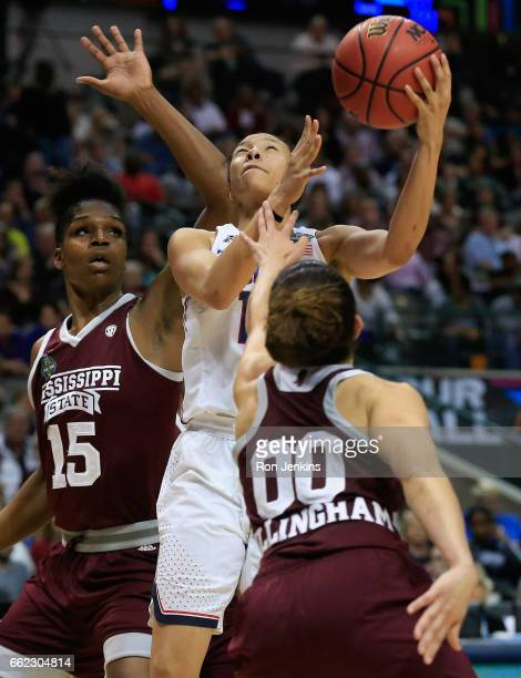 Saniya Chong of the Connecticut Huskies goes up for a shot against Teaira McCowan and Dominique Dillingham of the Mississippi State Lady Bulldogs in...