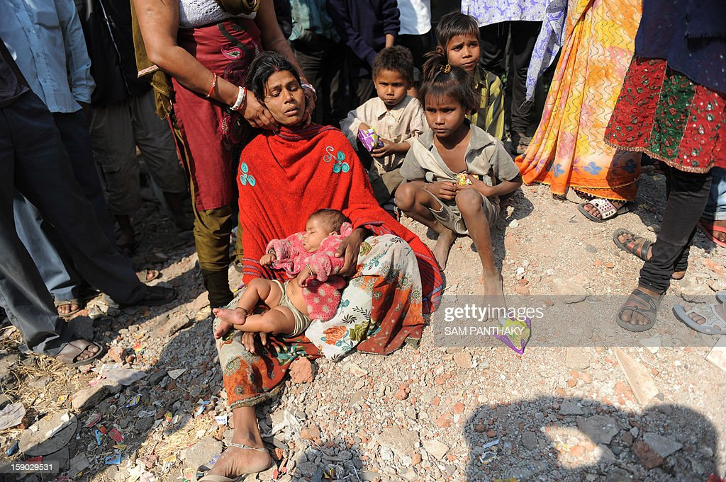 Sanju Devi, (C) wife of missing worker Jalandhar Chaudhari sits with her five children at the Indian Oil Corporation (IOC) plant at Hajira near Surat, some 275 kms from Ahmedabad on January 6, 2013. Three persons were killed in a major fire in a storage tank of IOC terminal, which was contained after a 21-hour operation by fire brigade team, officials said according to the Press Trust of India (PTI). AFP PHOTO / Sam PANTHAKY