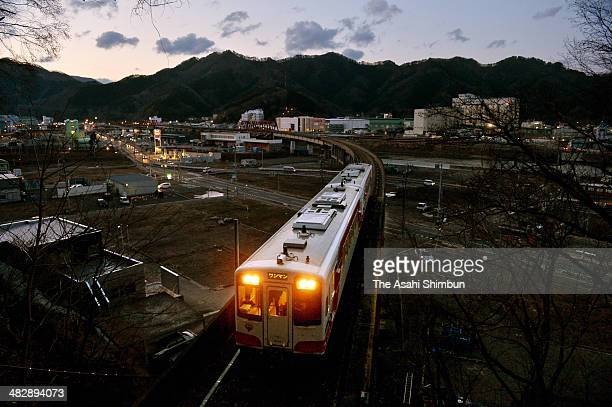 A Sanriku Railway train runs at the city center of Kamaishi City where the restoration work continues on April 5 2014 in Kamaishi Iwate Japan A local...