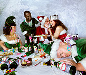 Santa and helper partying with elves, one elf sleeping at table