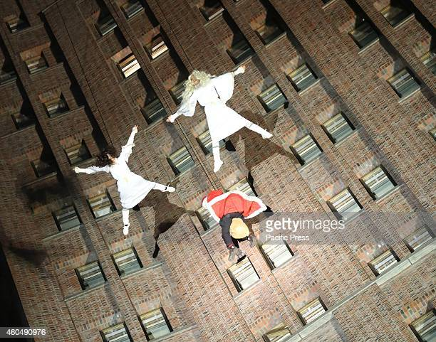 Santa Claus and angels abseil rappel in 100 meters on the facade of the Kollhoff Tower in Berlin after the distribution of gifts in the cafe