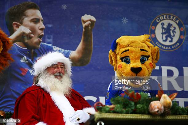 Santa Claus and Chelsea mascot Bridget the lioness welcome fans outside the stadium prior to the Barclays Premier League match between Chelsea and...