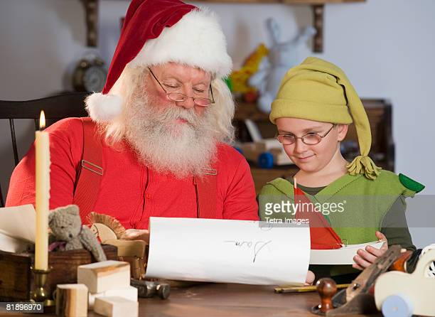 Santa Claus and elf reading list of names