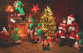 Santa Claus and little elves before Christmas in his house by fireplace and Christmas tree