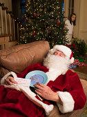 Santa Claus asleep on coach, girl (8-9) peeking from behind tree