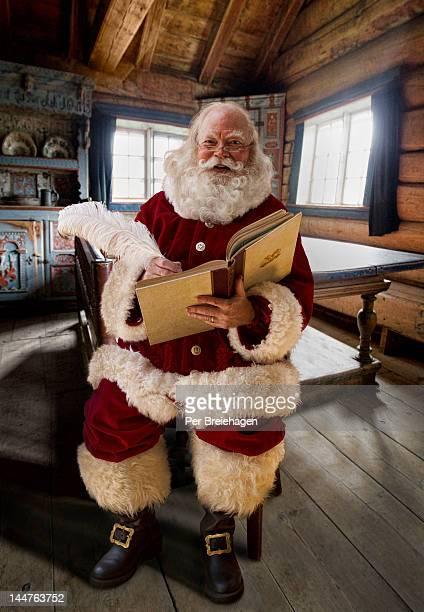 Santa Claus at home writing in his big book