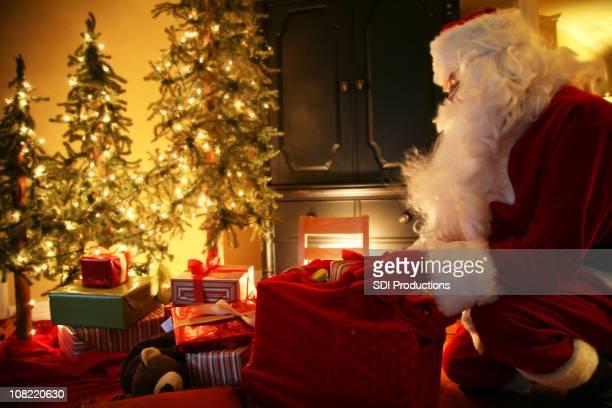 Weihnachtsmann bringt Geschenke in einem Hause am Heiligabend
