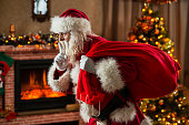 Santa Claus sneaking into home with finger on his lips and bringing Christmas presents.