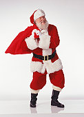 Santa Claus carrying bag of Christmas gifts, portrait
