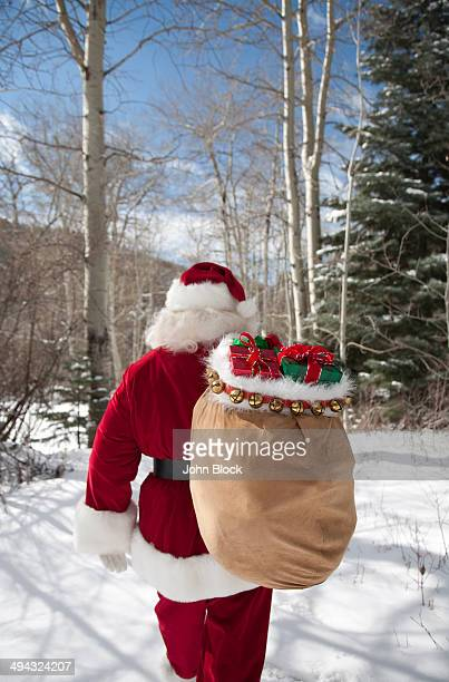 Santa Claus carrying Christmas gifts in snowy woods