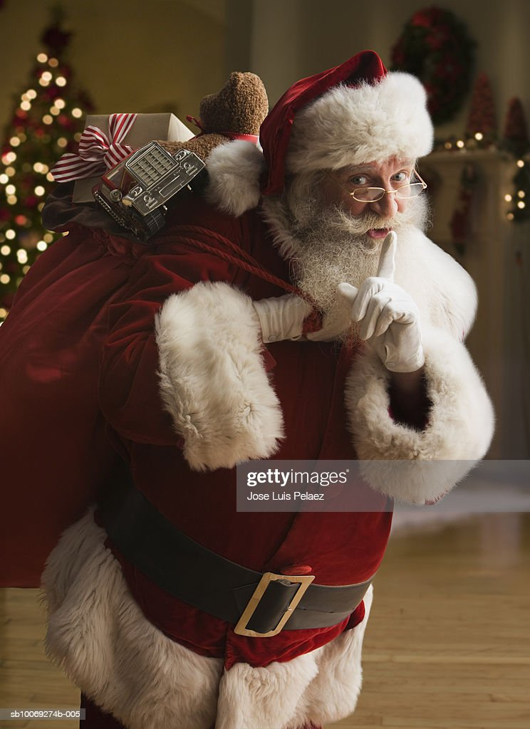 Santa Claus carrying sack of gifts with finger on lips, portrait, close-up : Stock Photo