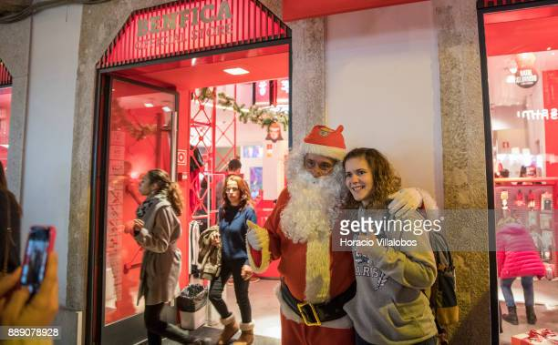 Santa Claus clad performer poses for pictures with a young tourist outside Benfica FC official store under Christmas and New Year light displays in...