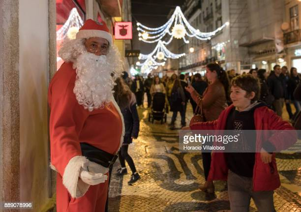 Santa Claus clad performer stands outside Benfica FC official store under Christmas and New Year light displays in Rua Augusta on December 9 2017 in...