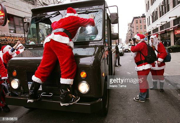 Santa Claus climbs on a UPS truck on 44th Street while others participate in the 2004 Santacon December 11 2004 in New York City The annual event...