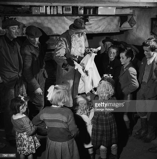 Santa Claus distributes presents to the children during Christmas in Ireland circa 1955