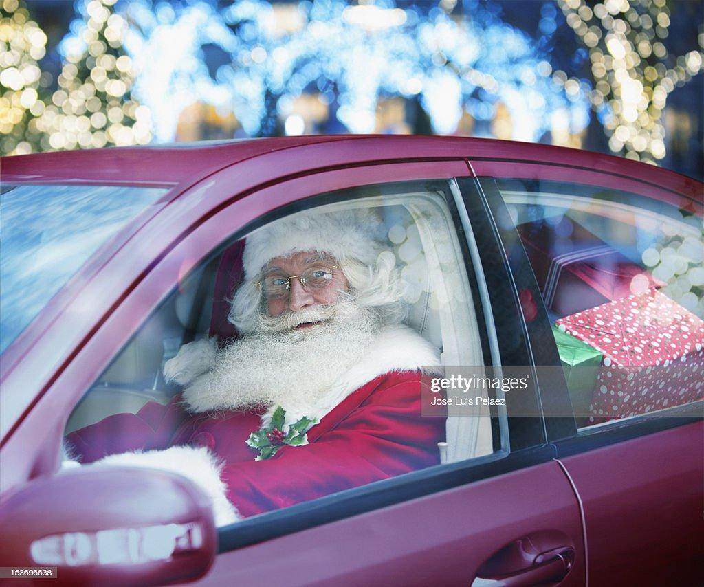 Santa claus driving a car full of presents : Stock Photo
