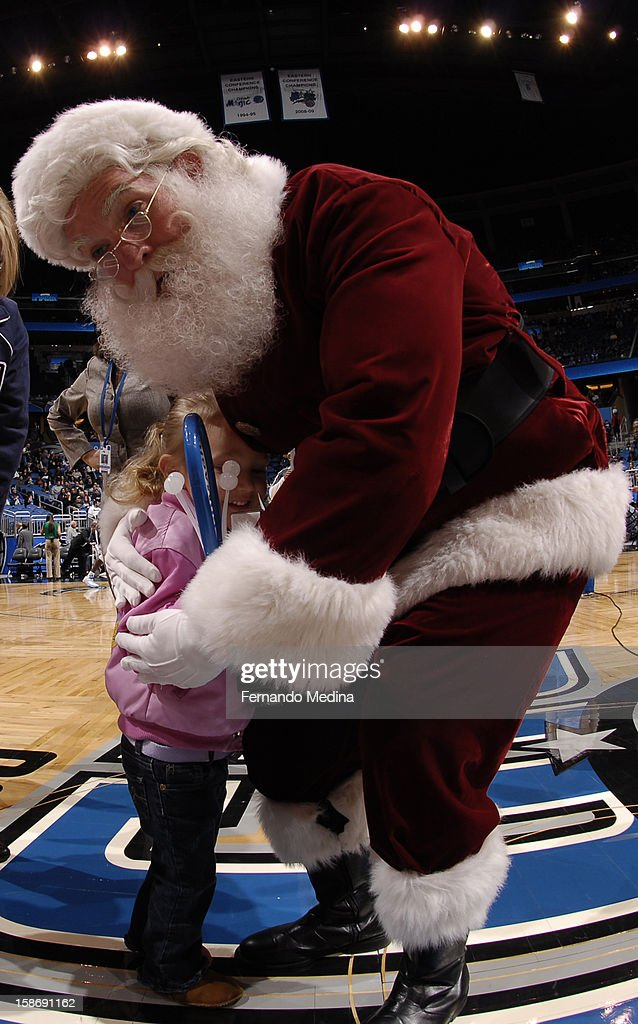 Santa Claus enjoys a moment with a little fan at half court prior to the Utah Jazz ,Orlando Magic game on December 23, 2012 at Amway Center in Orlando, Florida.