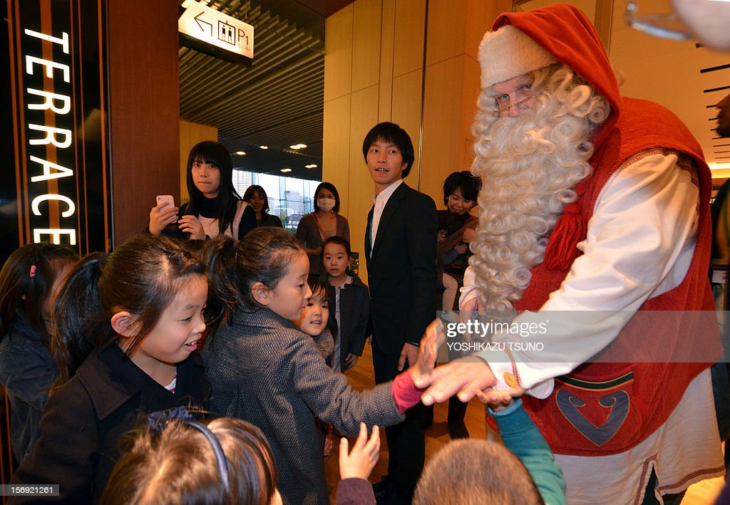 A Santa Claus from Lapland, Finland walks with children inside a shopping mall in Tokyo on November 25, 2012. Shoppers enjoyed a Christmas atmosphere with hundreds of thousands of LED lights illumination. AFP PHOTO / Yoshikazu TSUNO
