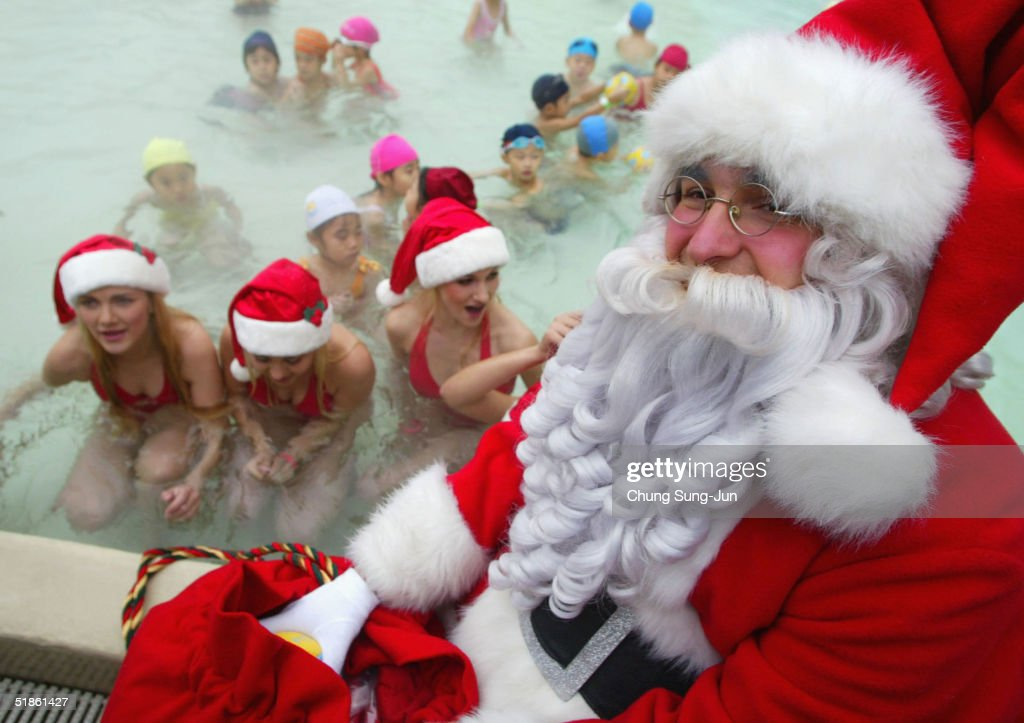 Santa Claus gives gifts to bikini clad models and South Korean children during a promotion for the upcoming Christmas holiday season at Everland...