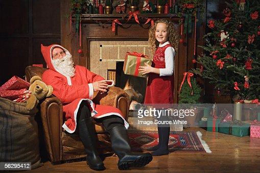 Santa Claus giving girl a gift : Stock Photo